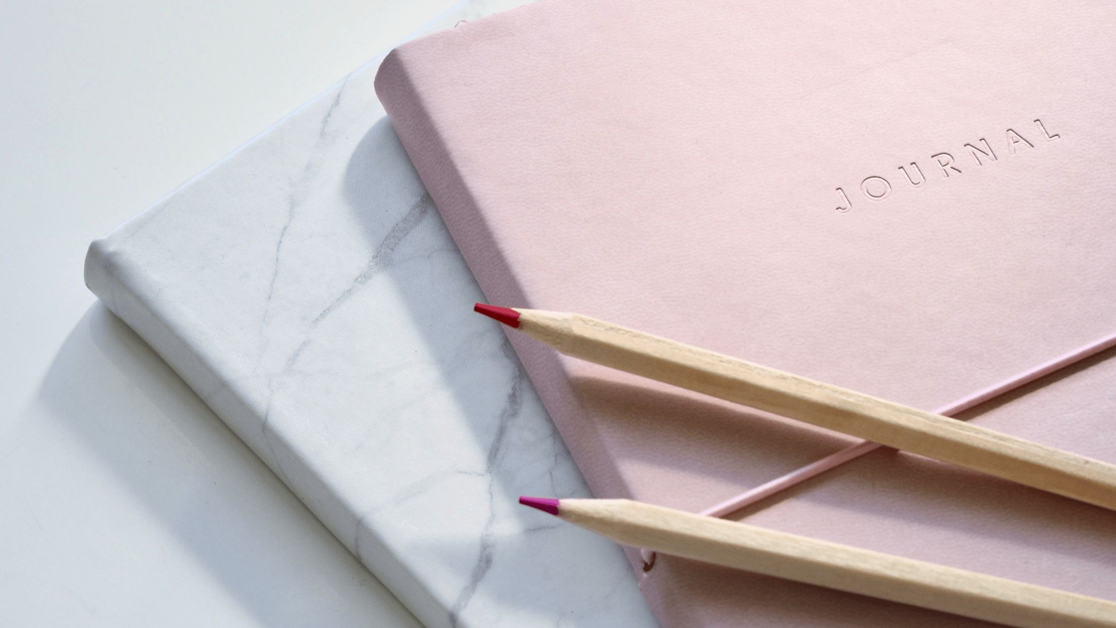 grey and pink journal on a white table