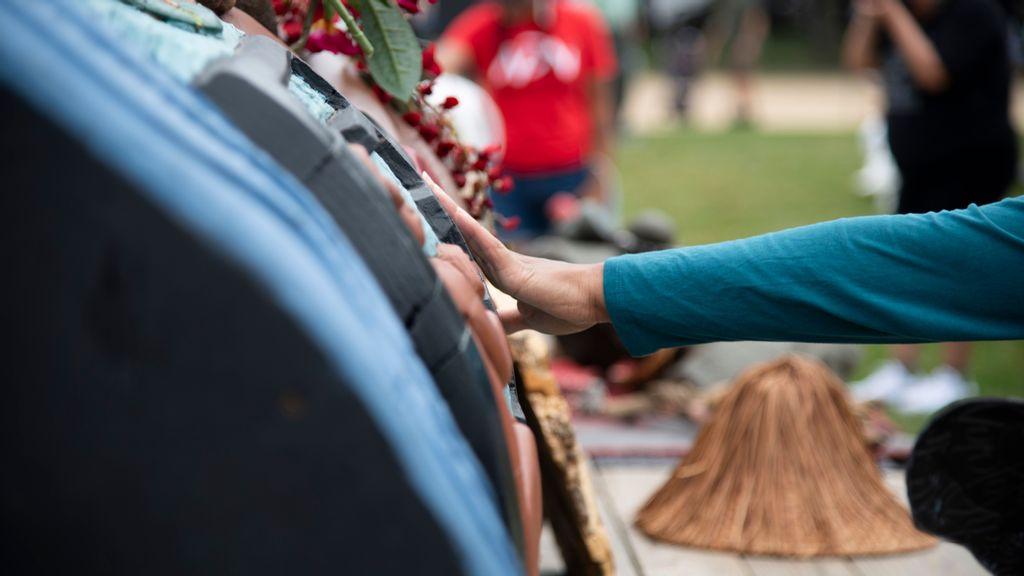 The Lummi Nation transported a 25-foot long totem pole from Washington state to the entrance of the U.S. Capitol.  A woman lays her hand on the totem after a call to pray and empower the 400-year-old cedar. (Zoey Zou/Zenger)